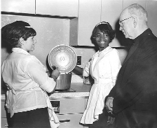 In 1958, the Archbishop Boland Rehabilitation and Training Center in Newark was established as a branch of the Mt. Carmel Guild. Vocational rehabilitation and occupational training services in home management, nurse's aide, dietary aide and power sewing were offered to eligible residents in the Newark Archdiocese. Archbishop Boland is pictured here with two trainees. Today, the Workforce Development program for disabled and disadvantaged clients continues to serve needs at the Boland Center.